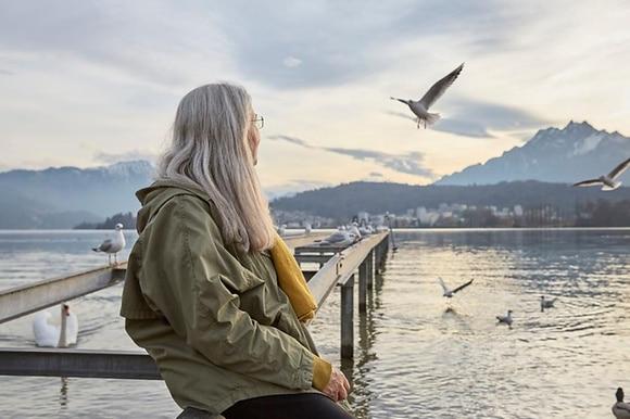 Un anziana in riva a un lago osserva dei gabbiani in volo.