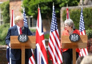 Trump e May ai rispettivi pulpiti si guardano e si sorridono; dietro, 3 bandiere USA e 3 UK alternate