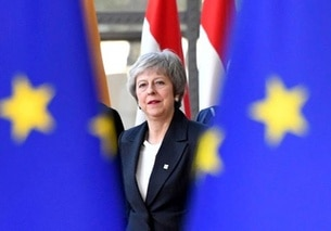 Theresa May davanti a due bandiere europee
