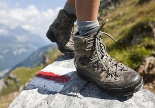 Walking boots on a rock with a mountain hiking trail sign