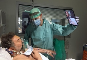 Man holds tablet for patient to talk to his relatives from hospital