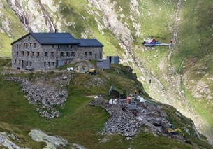 A helicopter transports material for the construction of the water purification system of the SAC s Terri Mountain Hut