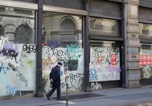 Un anziano signore cammina in centro di Milano davanti a negozi chiusi per fallimento.