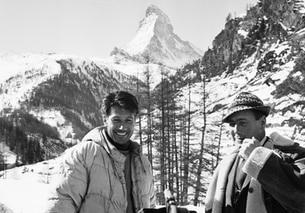 Persona sorride mentre è filmata, Cervino sullo sfondo.