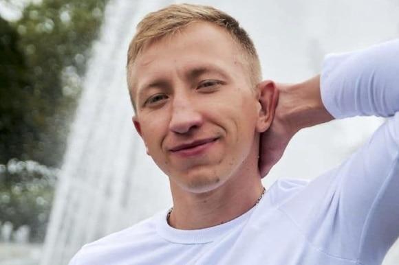 primo piano di uomo biondo con maglietta bianca con braccio sinistro dietro alla nuca